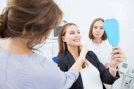 Young female patient, selects the color of the tooth, crown, veneer, looking in the mirror in the dental clinic. The concept of medicine, dentistry and health