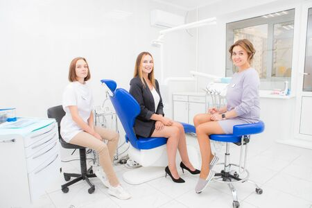 Two young women dentist and patient in the treatment room looking into the camera and smiling