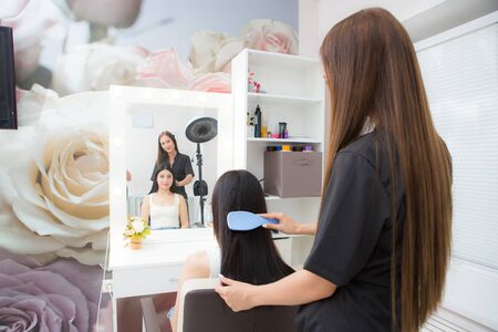 young woman hairdresser inspects client hair in a beauty salon