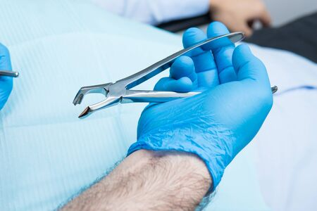 dentist hand in blue gloves with tooth extraction forceps