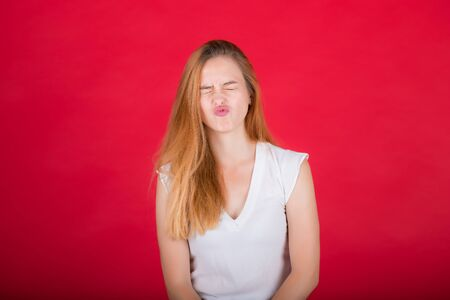 Young woman grimaces at the camera. Girl in a white shirt on a red background. Banque d'images - 135469216