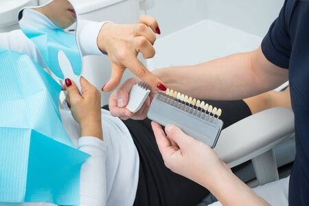 Woman patient points to the palette of teeth for choosing the color that the dentist holds in her hands
