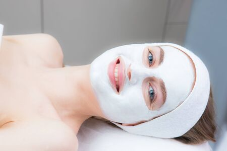 beautiful young woman with a cosmetic mask on her face lies in a beauty salon. Beautiful smile, blue eyes