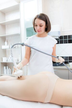Hardware cosmetology. Body care. Ultrasound cavitation body contouring treatment. Woman getting anti-cellulite and anti-fat therapy in beauty salon.
