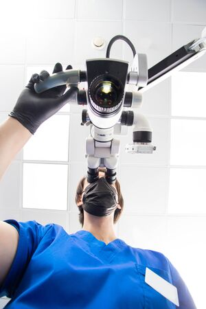 A male dentist is looking into a dental microscope. Bottom view.
