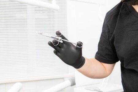 Dentists hand in a black glove holding a dental syringe. for local anesthesia Фото со стока