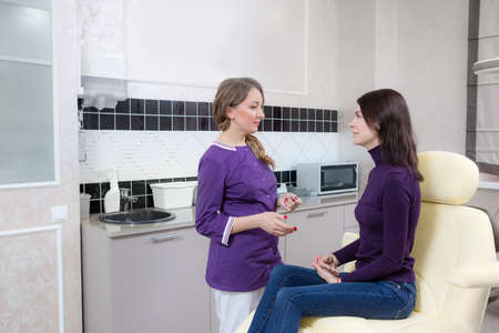 Professional cosmetologist. young woman talking to her customer while working in the beauty clinic