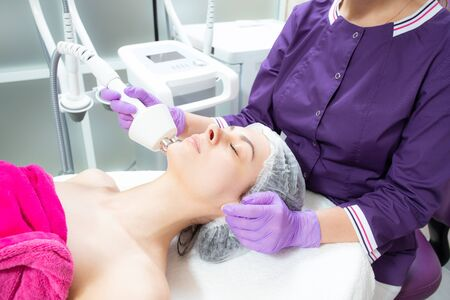Portrait of a woman getting rf lifting. The lifting procedure in the beauty salon. Cosmetology, skin care