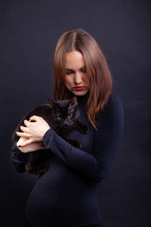 Portrait of a red-haired young woman in black clothes on a black background with a black cat in her arms