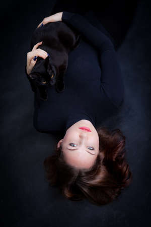 red-haired young woman lies in black clothes on a black background with a black cat in her arms Фото со стока