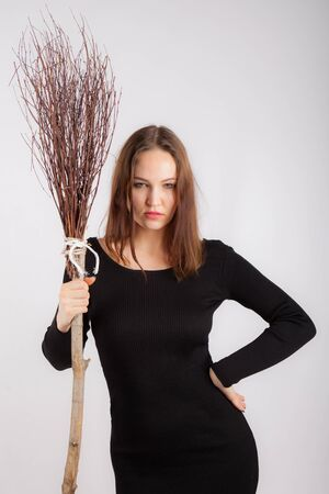 portrait of a sexy young woman with a broom
