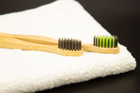 Bamboo toothbrushes with a white towel on a black background. Biodegradable natural bamboo toothbrush. Eco-friendly, zero waste, dental care No plastic Фото со стока