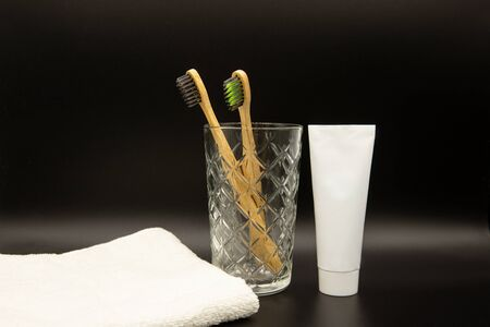 natural bamboo toothbrushes in a glass cup. Toothpaste and towel. Black background.