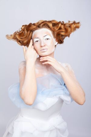 Image of a young beautiful red-haired woman. Young woman with an unusual hairstyle and unusual make-up.