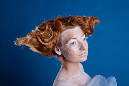 Portrait of a young red-haired woman with big curls. Bright creative makeup, unusual hairstyle