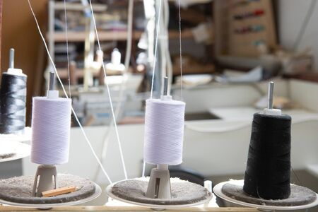 spools of white and black thread stand on a sewing machine. Фото со стока
