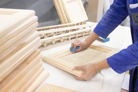 diligent female carpenter sanding wood at the workshop