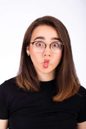 funny beautiful girl in glasses makes lips a bow. Studio photo