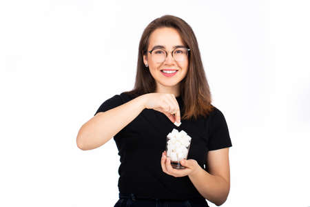 young beautiful woman holding a glass with sugar in her hand