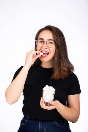 Beautiful young woman holding a glass with sugar in her hand and white teeth biting a piece of white sugar