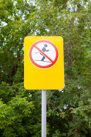 Sign prohibiting skiing. Against the background of green plants Фото со стока