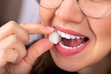 Beautiful woman mouth with big white teeth bites on a white sugar cube Banco de Imagens