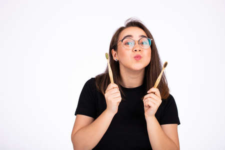 Portrait of a young beautiful woman in glasses holding two toothbrushes isolated on white Фото со стока