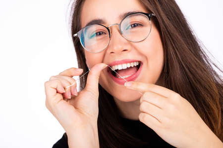 Young beautiful woman in glasses using dental floss on white background Фото со стока