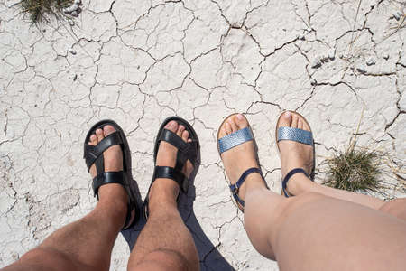 Male and female feet in open shoes, sandals. View from above. They stand on dry ground with cracks, a little dried grass. Heat, heat. Фото со стока