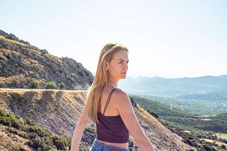 Young beautiful blonde woman looks at the horizon. The traveler stands in the mountains Фото со стока