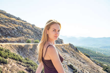 portrait of a young beautiful woman on a background of mountains