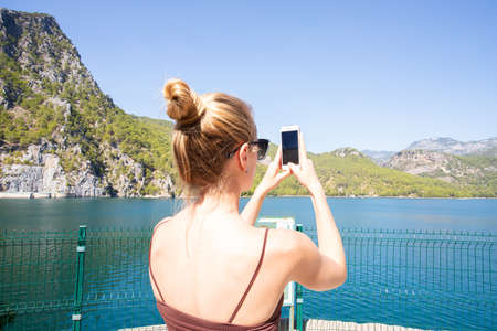 young woman in sunglasses photographs the panorama of a mountain lake on the phone. Travel
