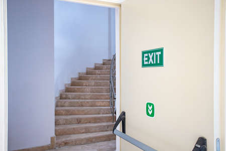 Emergency exit door with exit sign. Exit up the stairs. Fire escape in a modern building. Фото со стока
