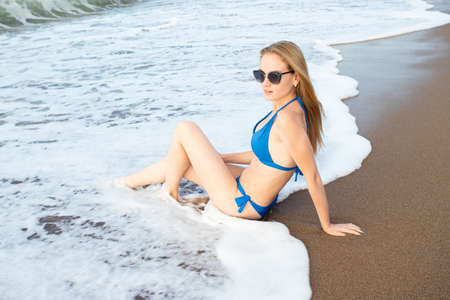 Sexy young blonde woman sunbathing by the sea. Sits on the sand in the surf zone wearing sunglasses