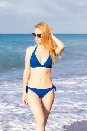 Beautiful young girl in bikini posing on the beach under the hot sun, outdoor portrait. Woman in sunglasses