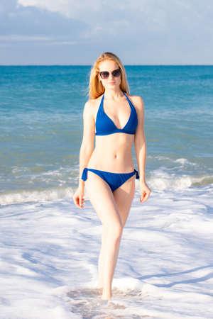 Beautiful young woman in sexy bikini standing on the sea beach wearing sunglasses