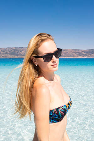 portrait of sexy young girl in sunglasses standing on the beach of a mountain lake. Young woman wearing sexy swimsuit