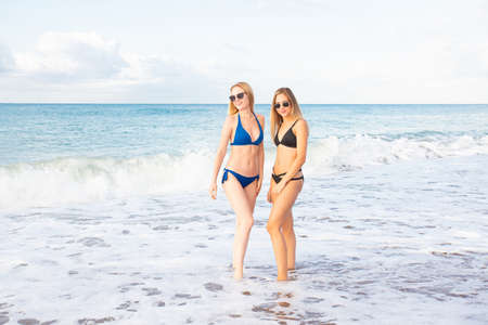 Two attractive sexy girls on the beach in bikini in sunglasses, against the background of the sea.