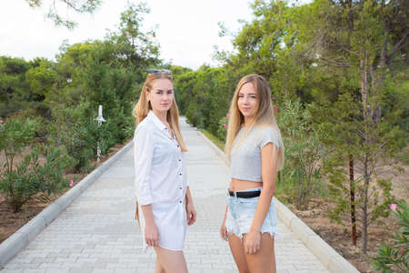 Two young female friends standing together in the park