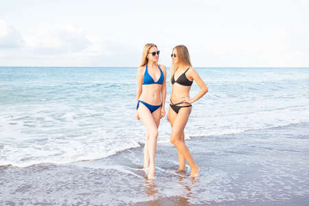 Two attractive sexy girls on the beach in bikinis look at each other through sunglasses, against the background of the sea.
