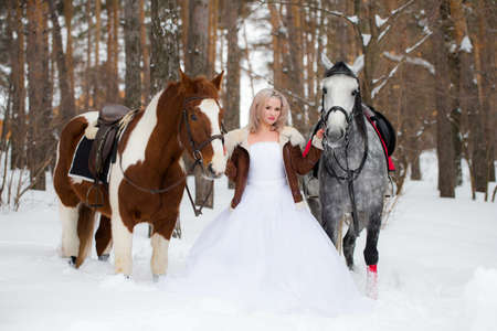 blond woman between horses outdoors in winter nature park. Portrait of a laughing woman with two horses. Friendship and pets concept. Фото со стока