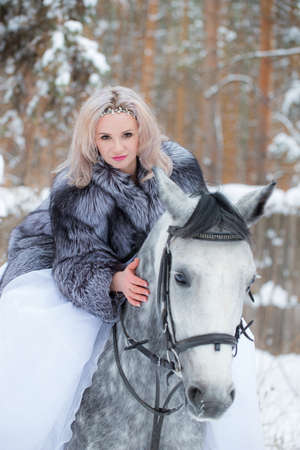 Young blonde in a fur coat, beautiful woman riding a light gray horse.