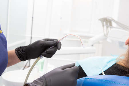 Dental assistant helping with saliva ejector during dentist treatment Фото со стока