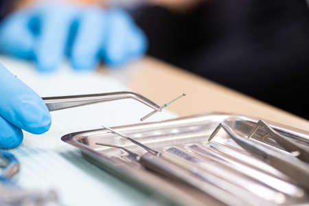 Dental instruments close up. the dentist holds a drill for a power drill with tweezers. Dental treatment.