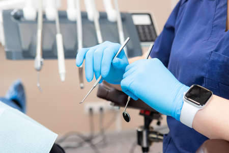 dental instruments in the hands of the doctor. Dentist in sterile latex gloves holding dental tools Close-up