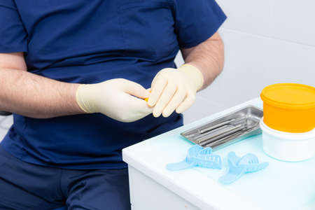 Dentistry. Prosthetics works. The dentist makes a blank for the impression of the denture of the jaw and teeth.