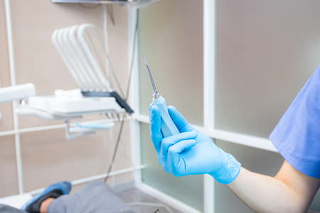 the dentist holds a tool for removing teeth in his hand. elevator Фото со стока