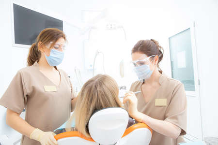 Patient with dentist and dental assistant wearing masks and gloves. Stock Photo