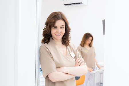 Portrait of pretty female dentist arms crossed with colleague standing in background