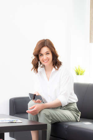 Portrait Of Businesswoman Sitting On Sofa In Modern Office